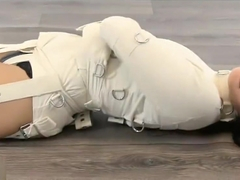 Girl trapped in straitjacket, bound legs.