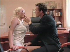 Adorable young blonde lies on the desk and takes a hard cock deep in her peach