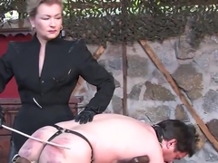 Lady with leathered miniskirt canes slave