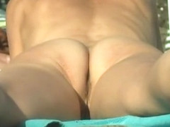 Small tattoos nudist woman sunbathing