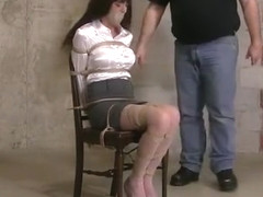 Girl with shiny blouse tied to a chair