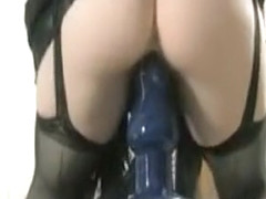 Gorgeous slut in lingerie squats on a large blue dildo and fucks it
