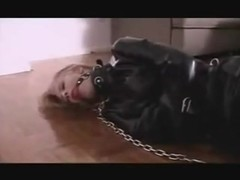 Slave in straitjacket chained struggles to door