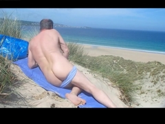 Male nudist spied massaging his butt  genitals in the dunes